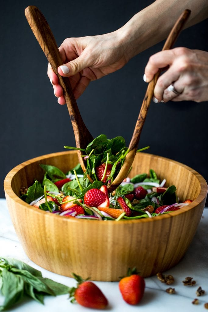 strawberry basil salad in a large wooden bowl
