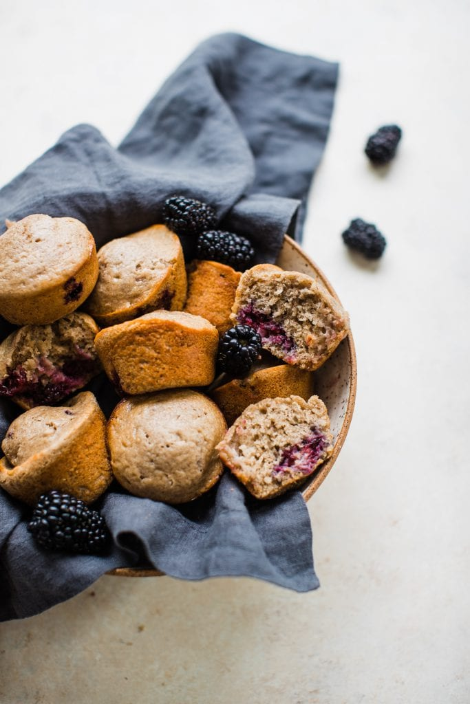 blackberry muffins in a bowl with a dark blue napkin