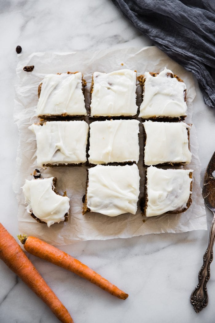 carrot cake bars cut into squares on parchment paper