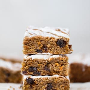 carrot cake bars with icing on parchment paper