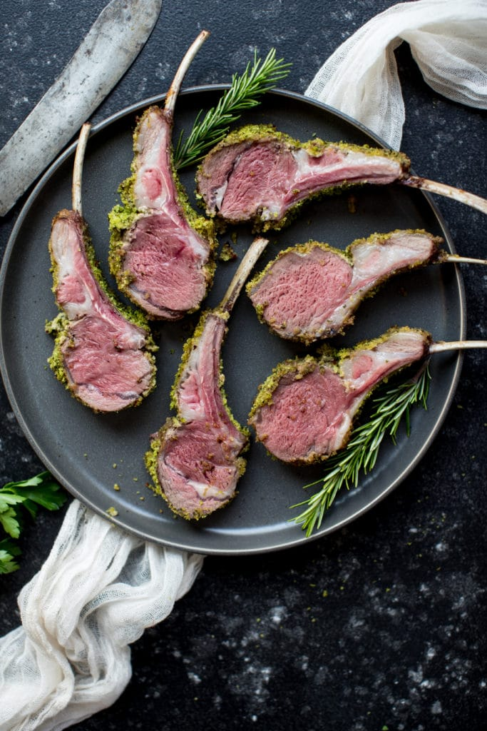 herb crusted rack of lame on a dark blue plate