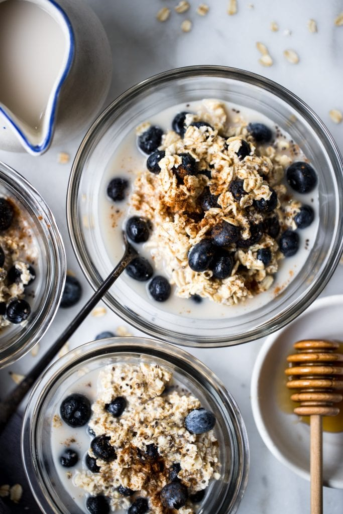 overnight oats made with oat milk topped with blueberries in glass bowls