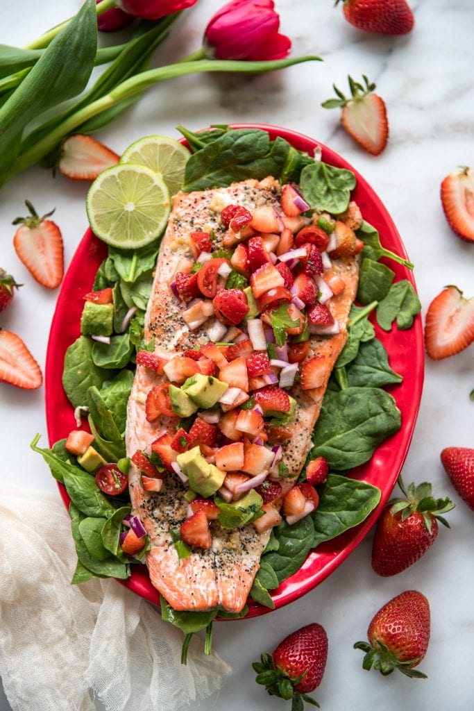 salmon on a bed of spinach on a red plate