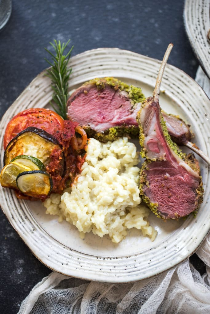 herb crusted rack of lamb with risotto and veggies on a white plate