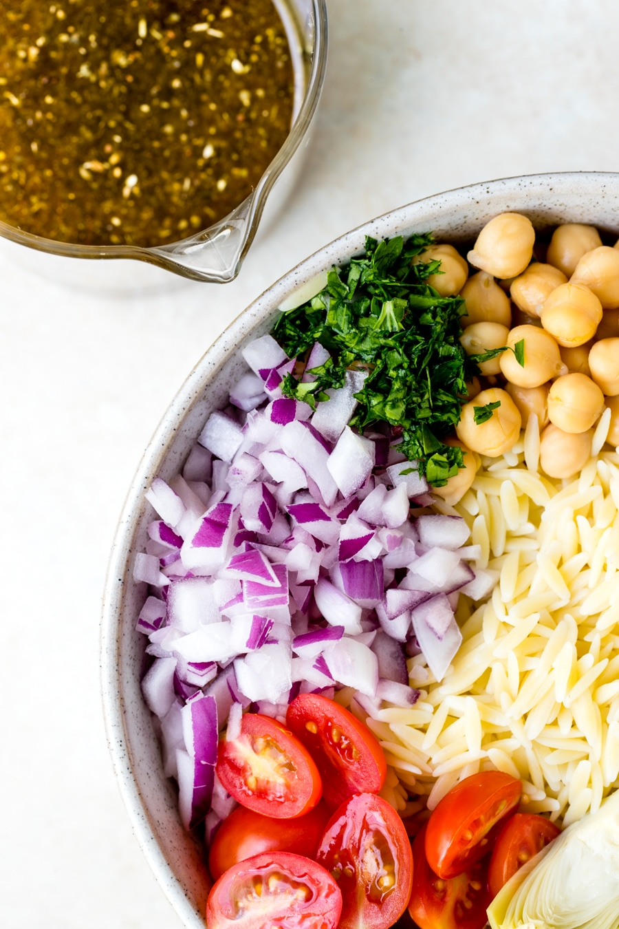 Orzo Salad Recipe in a large white bowl with red onion, cherry tomatoes, parsley and garbanzo beans