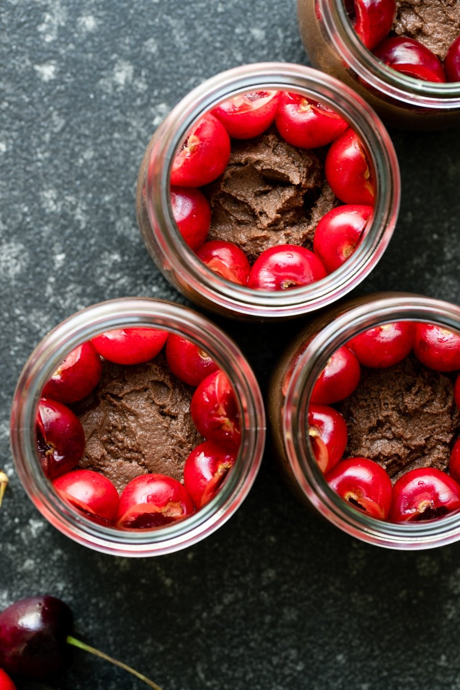 chocolate mousse in glass jars topped with cherries