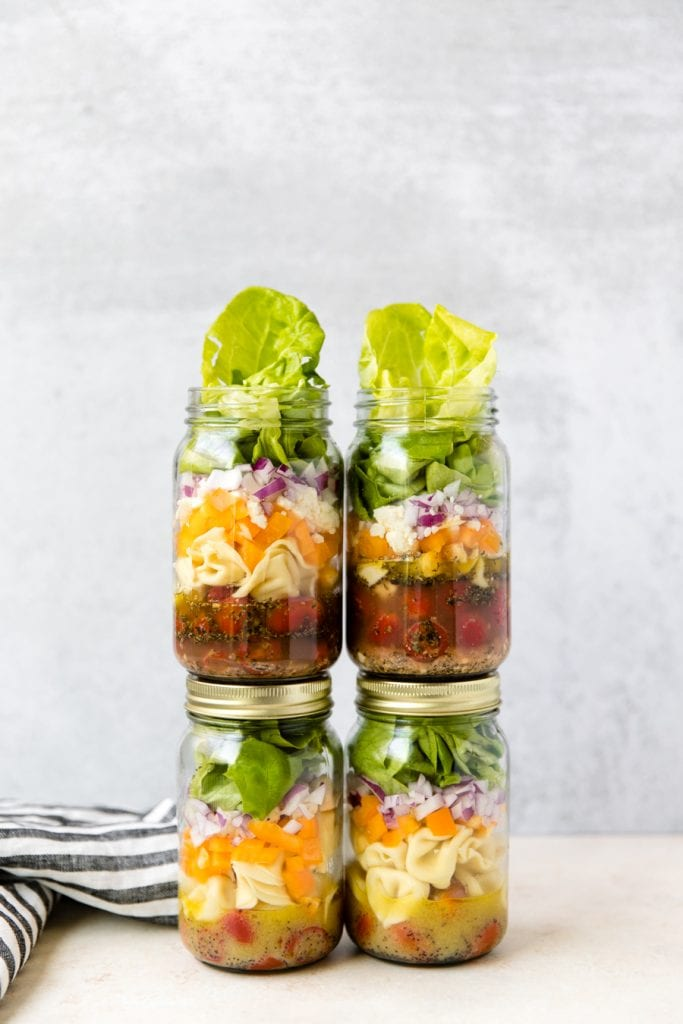 four mason jar salads stacked on top of each other