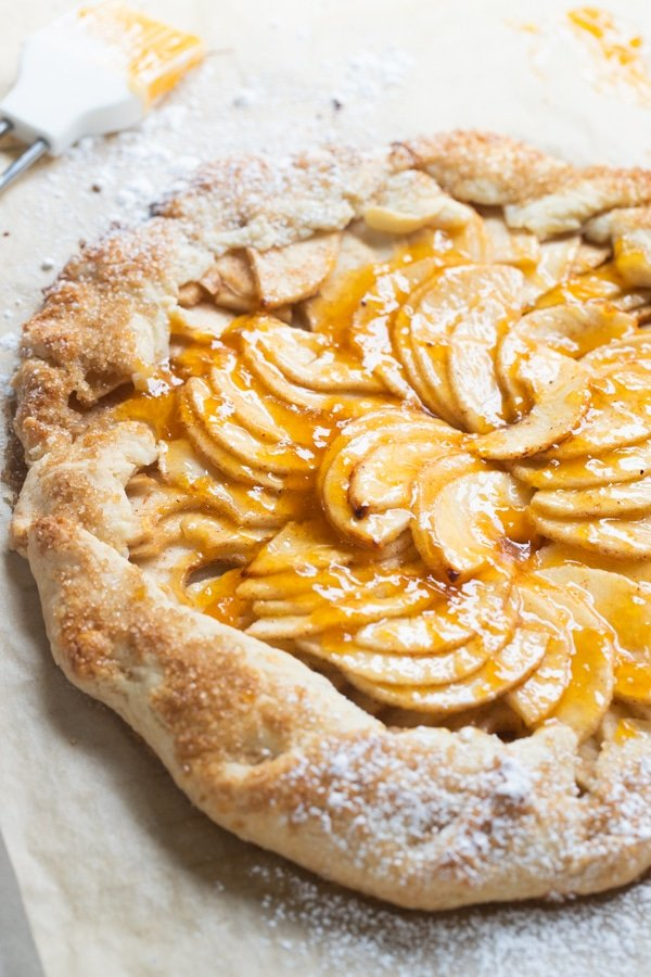 a baked apple galette on parchment paper with apricot jam