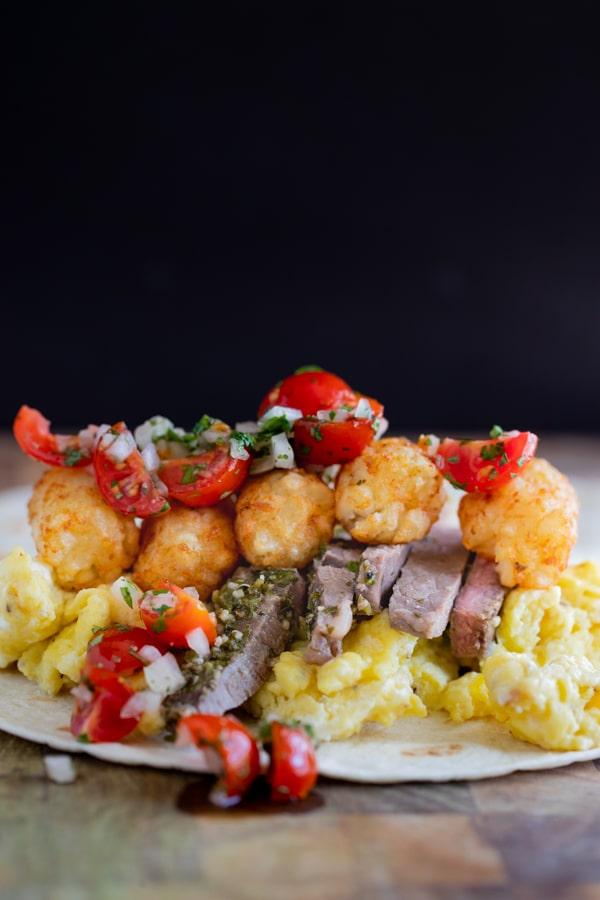 a breakfast burrito with carne asada steak, eggs, pico de gallo, tater tots and cheese