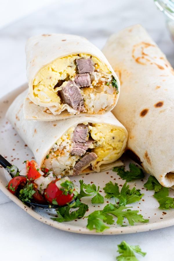 a carne asada burrito on a plate with cilantro and pico de gallo