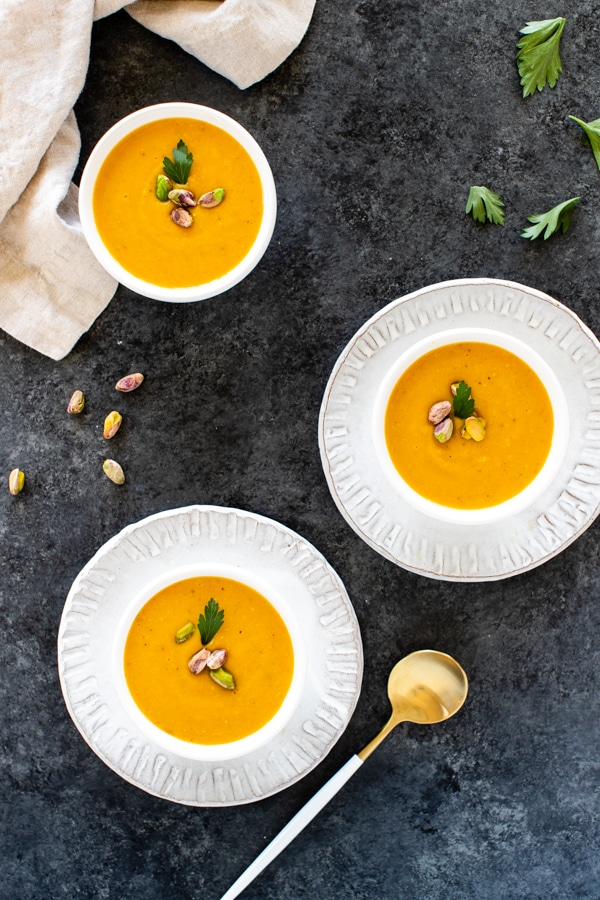 pistachio pumpkin soup in small white bowls topped with pistachios