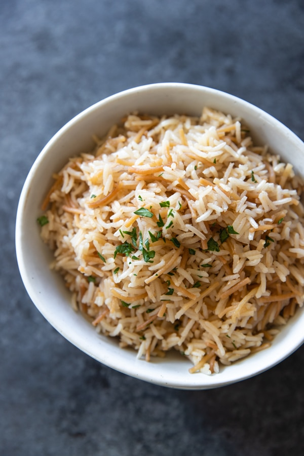 rice pilaf in a white bowl topped with chopped parsley
