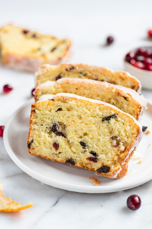 cranberry orange bread sliced on a white plate