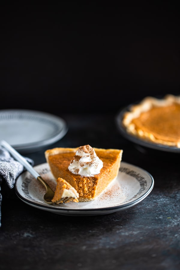 sweet potato pie on a white plate whipped cream on top