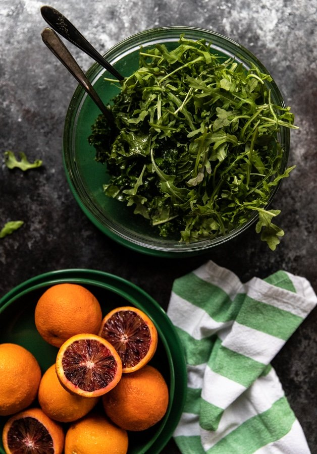 arugula and kale in a glass bowl on top of a green plate with a side of blood oranges