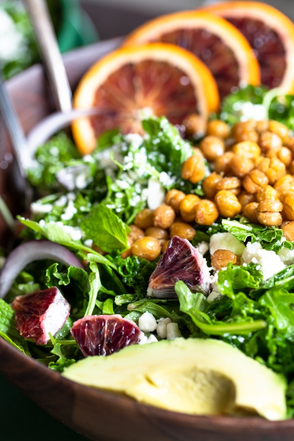 a green salad in a wooden bowl topped with chickpeas, avocado and blood oranges