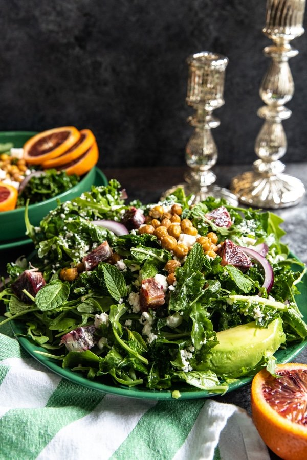 a winter blood orange salad with massaged kale and arugula on a green plate topped with mint and chickpeas