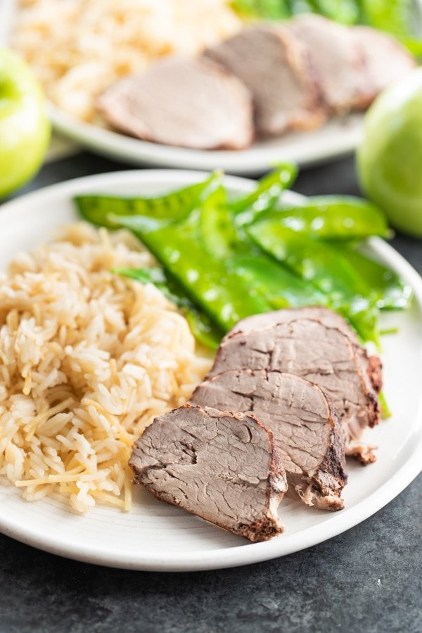 pork tenderloin on a white plate with rice