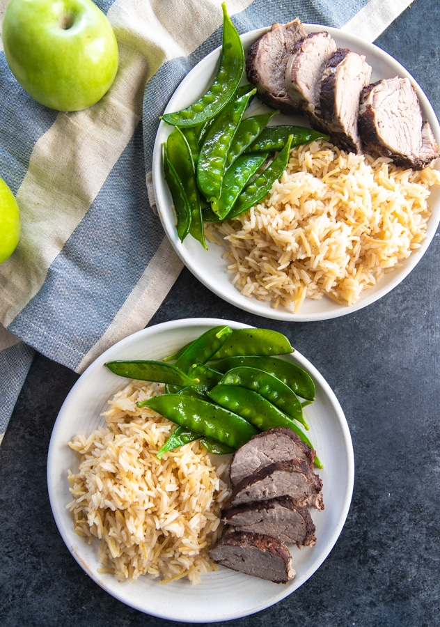 pork tenderloin on a plate with rice and snow peas