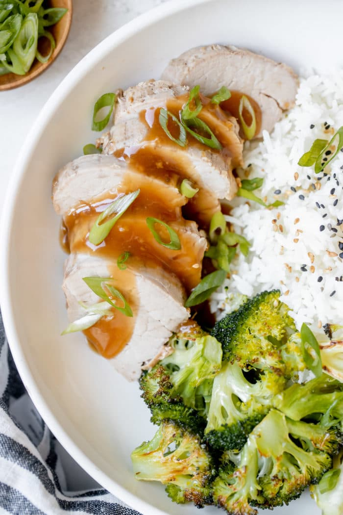 pork tenderloin in a white bowl with broccoli and rice
