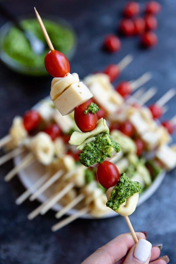 tortellini on a skewers with cherry tomatoes, jack cheese and spinach pesto