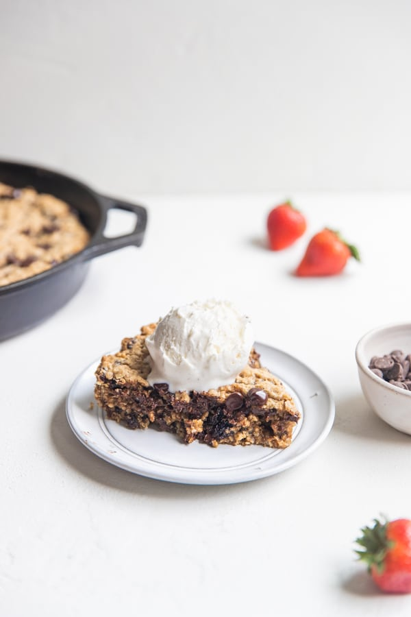 cookie skillet on a white plate topped with vanilla ice cream