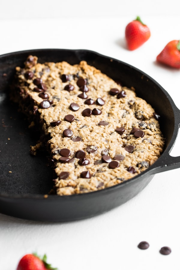 a chocolate chip cookie skillet in a cast iron skillet with strawberries
