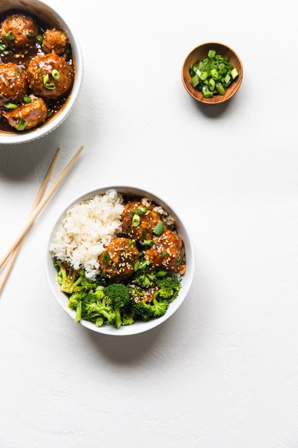 meatballs in a white bowl with broccoli and rice and green onions