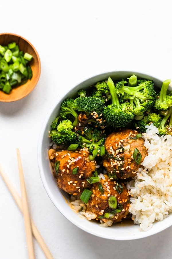 healthy meatballs in a white bowl with broccoli and rice
