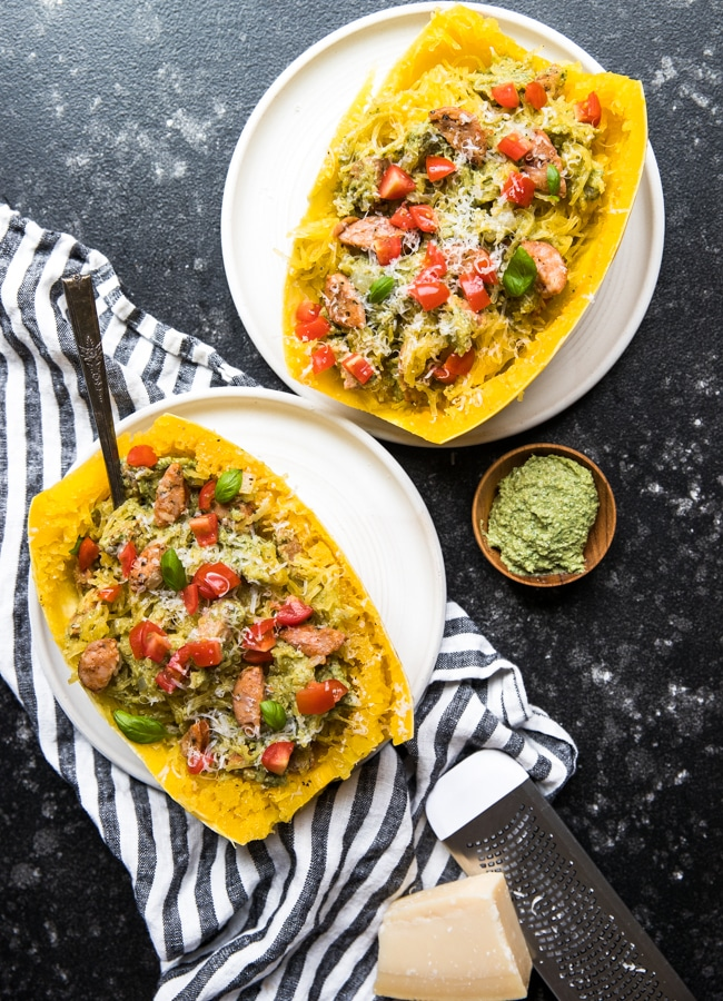 spaghetti squash boats filled with chicken sausage, vegan avocado pesto and topped with cherry tomatoes and basil on white plates