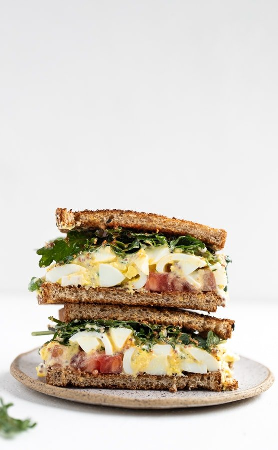 egg salad sandwich with baby kale, tomatoes and hot sauce