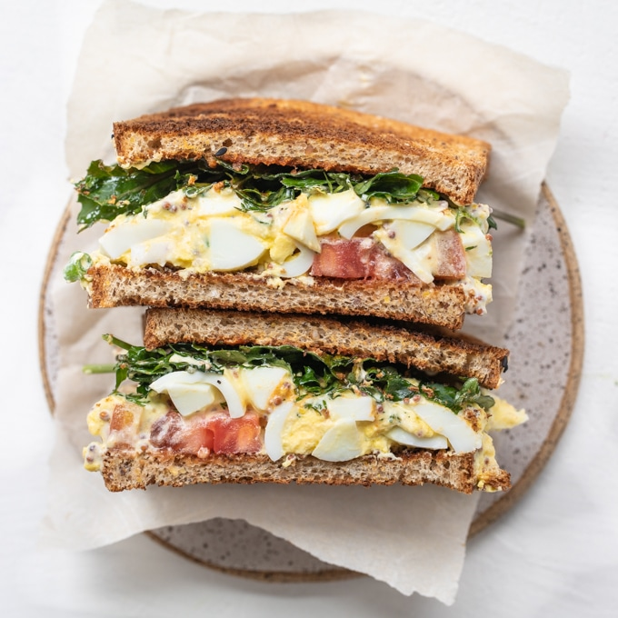 egg salad sandwich on wheat bread with baby kale, Dijon and heirloom tomatoes