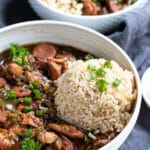 a white bowl filled with chicken and sausage gumbo topped with brown rice