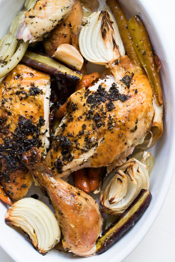 roast chicken carved and in a serving dish with roasted vegetables