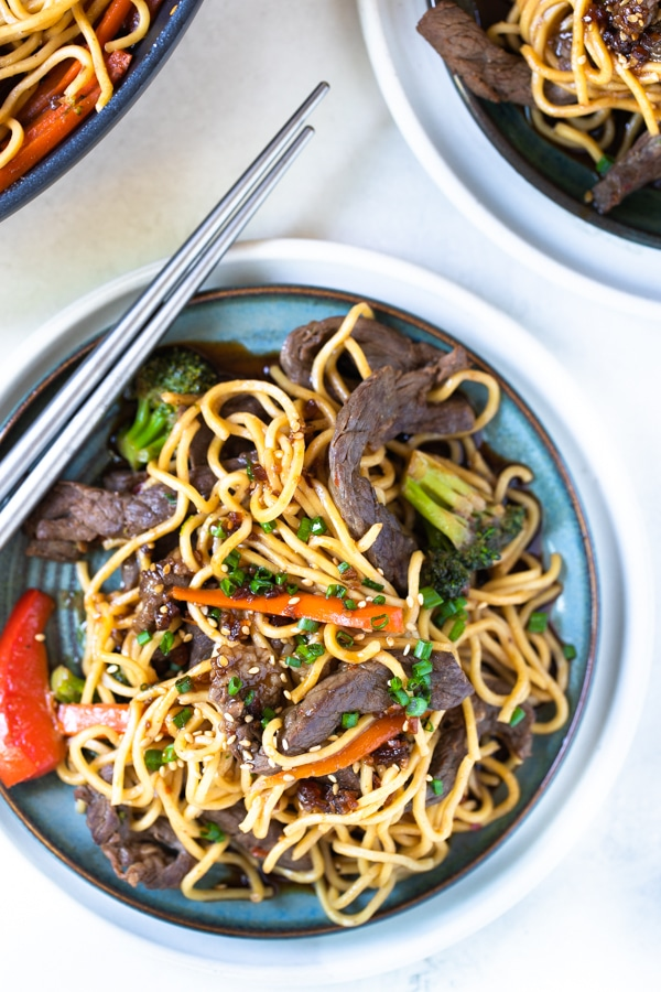 a blue plate with beef stir fry and ramen noodles