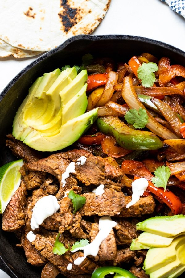 flank steak and bell peppers and onions in a cast iron skillet for flank steak fajitas