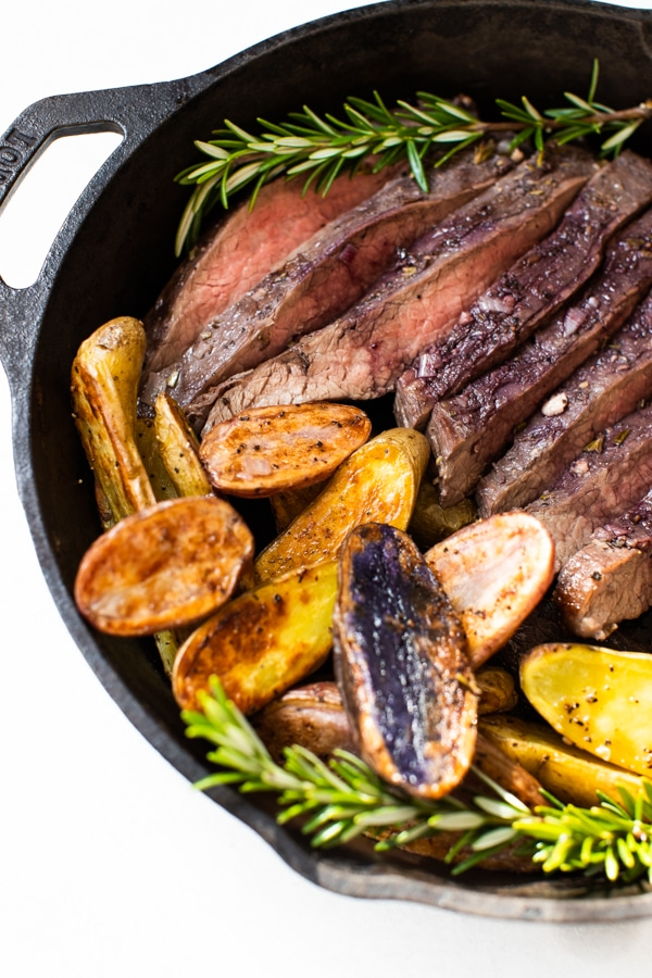 baked flank steak and fingerling potatoes in a cast iron skillet