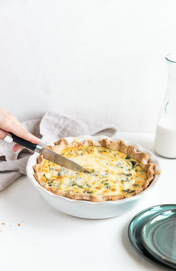 slicing into a quiche Florentine with a knife
