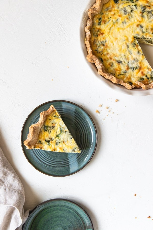 a slice of quiche Florentine on a blue plate