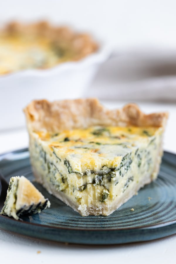 quiche Florentine on a blue plate with a bite taken from it.