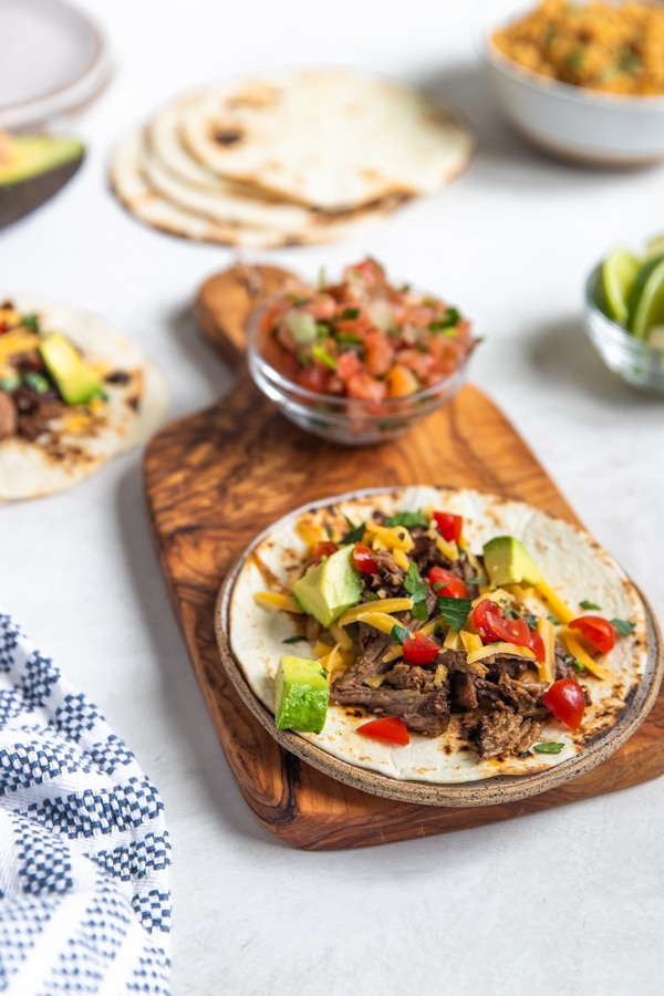 shredded beef tacos on a flour tortilla