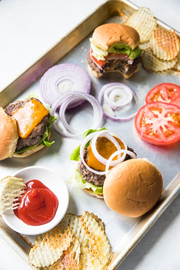 delicious homemade ground beef burgers with all of the toppings on a sheet pan