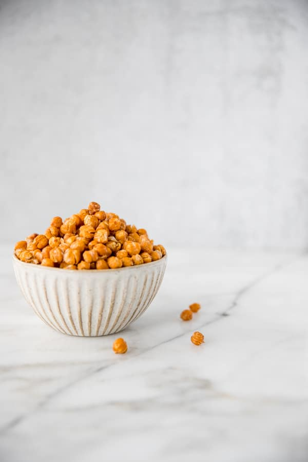 a bowl of roasted chickpeas on a marble table