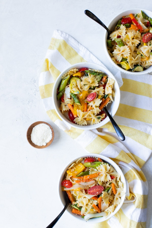 healthy pasta primavera in white bowls