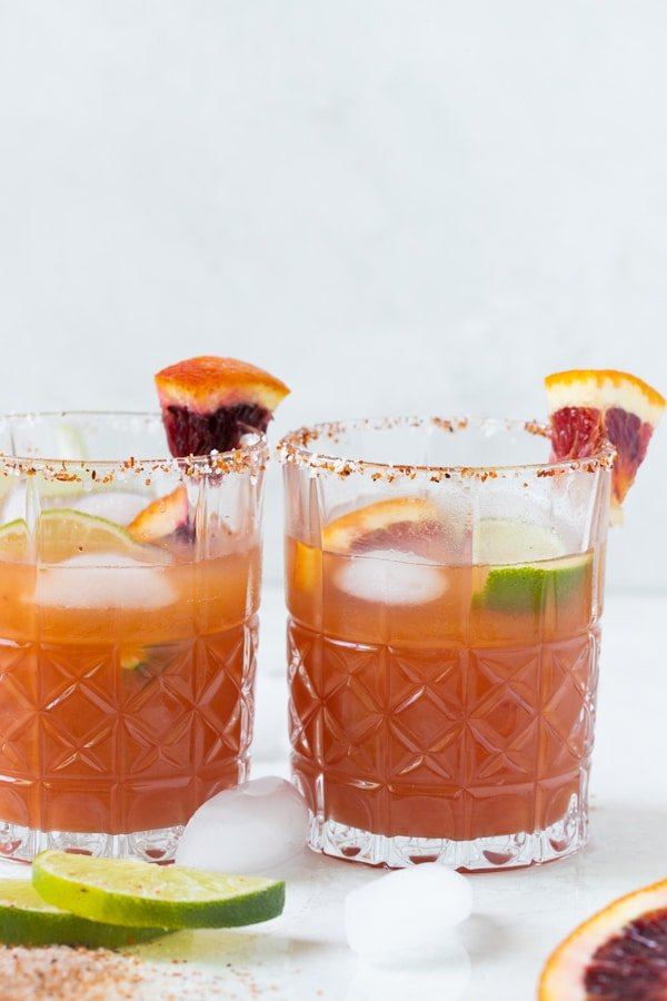blood orange margarita in a low ball glass with a blood orange garnish