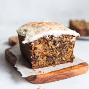 A piece of carrot cake sitting on top of a wood cutting board