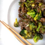 beef and broccoli with noodles in a white bowl
