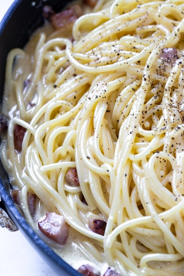 spaghetti carbonara in a non stick frying pan garnished with black pepper
