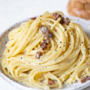 spaghetti carbonara on a speckled plate garnished with black pepper