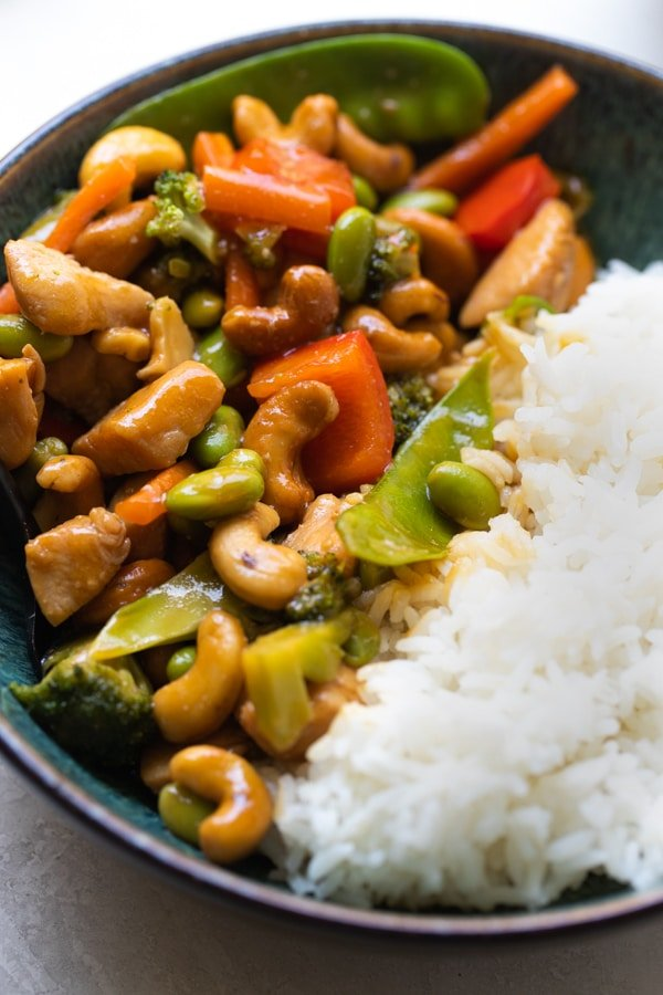 cashew chicken stir fry in a blue bowl with white rice